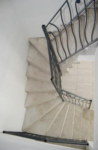 Escalier béton deux quarts tournants avec rambarde en fer forgé vu d'en haut